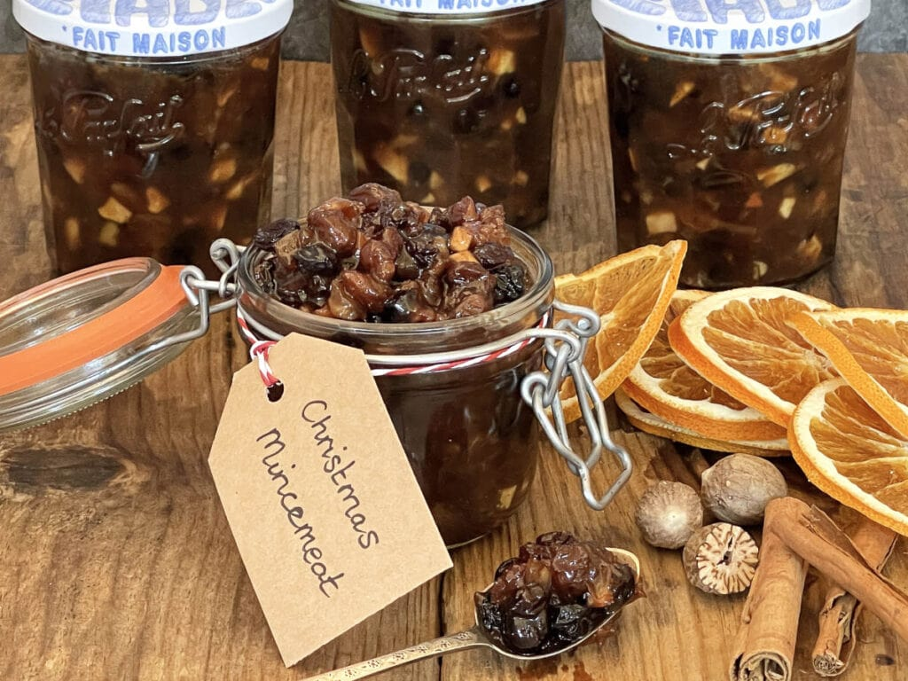 Jars of Slow Cooker Christmas Mincemeat with dried citrus slices and spices.