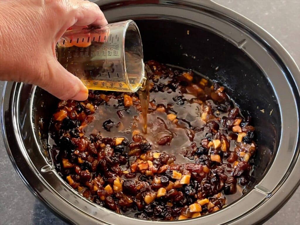 Calvados pouring into a slow cooker.